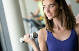 Happy fit fitness girl exercising indoor in fitness center