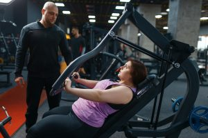 Overweight woman with trainer doing exercise, gym