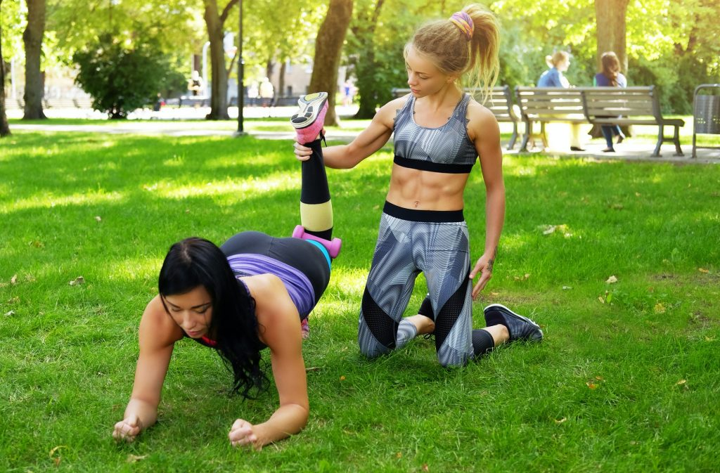 Workout at the park outdoors, girl with her coach doing exercises on the grass.